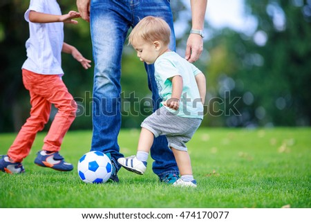 Father and sons playing football in park