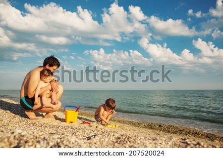 father and sons playing in sand on the beach  - stock photo