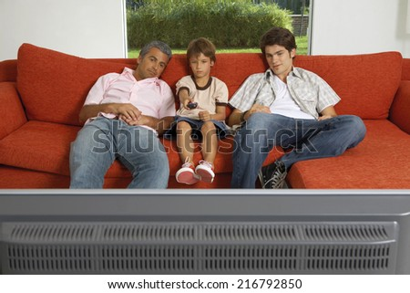 Father and sons watching TV. - stock photo
