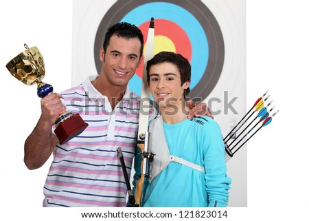 father and teenage after victory in arbalete championship - stock photo