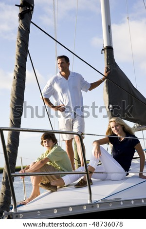 Father and teenage children relaxing on sailboat at dock on sunny day - stock photo