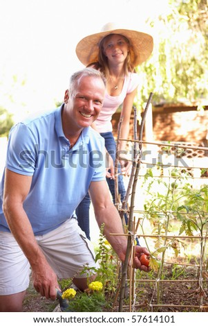 Father And Teenage Daughter Relaxing In Garden - stock photo