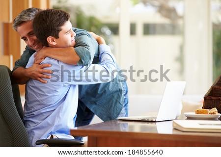 Father And Teenage Son Having A Hug - stock photo