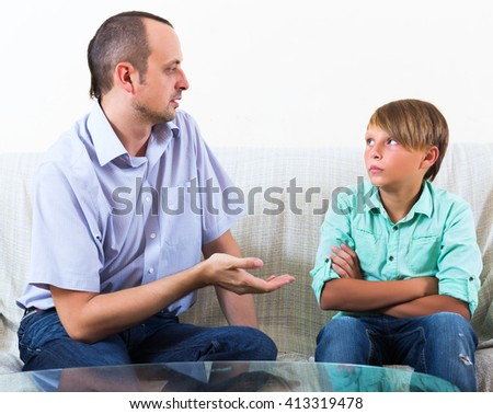Father and teenager discussing something serious at home - stock photo