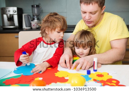 father and the children prepare together Paper decor. children's creativity. Tools and materials for children's art creativity on table. Easter decor.