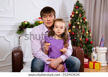 Father and the daughter on Christmas, sitting near a fir-tree - stock photo