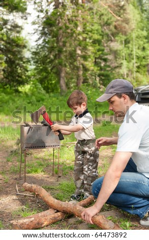 Father and the son on a nature cut wood for a fire