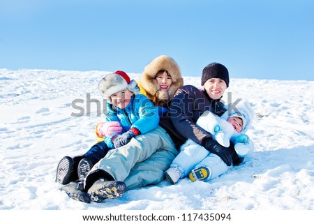 Father and three kids on a snowy hill - stock photo