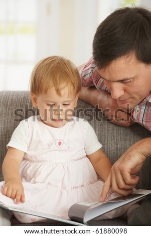 Father and toddler reading book on sofa at home.?