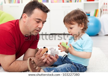 Father and toddler son playing on the floor with finger puppets - stock photo