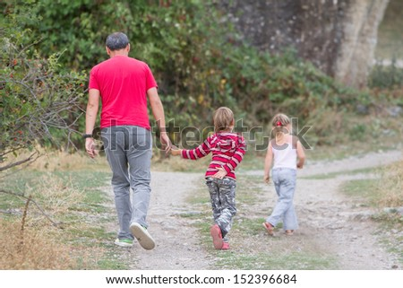 father and two children boy and girl walking on natural background