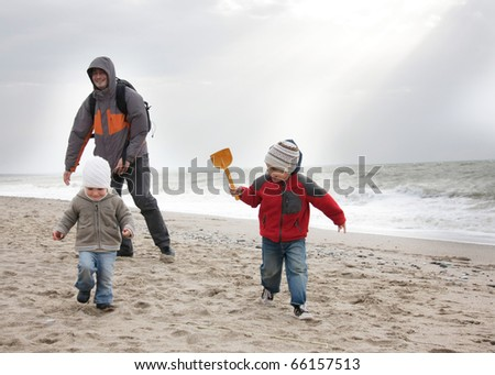 father and two children playing on beach