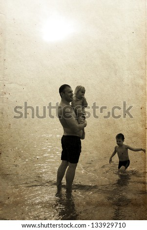 Father and two kids on the beach at sunset. Photo in old image style - stock photo