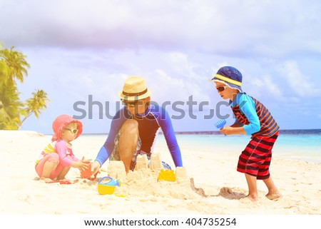 father and two kids playing with sand on beach - stock photo