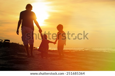 father and two kids walking on beach at sunset