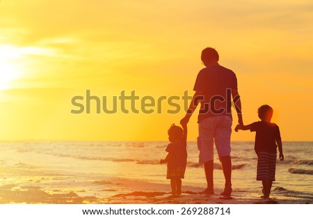 father and two kids walking on beach at sunset - stock photo