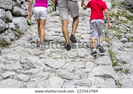 Father and two kids walking on the mountain trail - stock photo