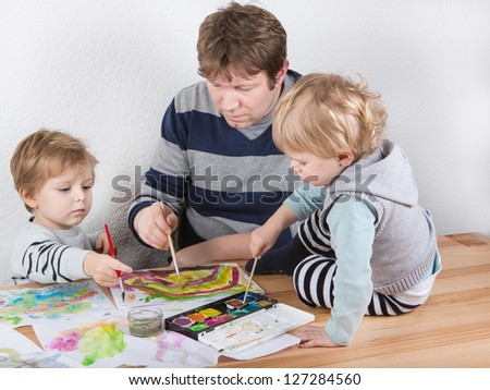 Father and two little boys siblings having fun painting at home