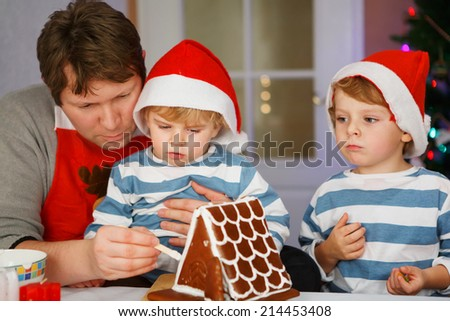 Father and two little sons preparing a gingerbread cookie house at christmas time - stock photo