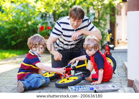 Father and two little sons reparing bikes together, outdoor. - stock photo