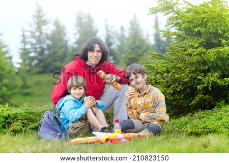 father and two sons have got picnic in the mountains