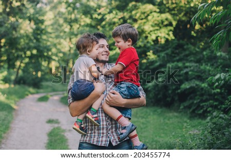 Father and two sons having fun outdoors - stock photo
