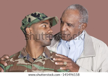 Father and US Marine Corps soldier looking at each other over brown background - stock photo