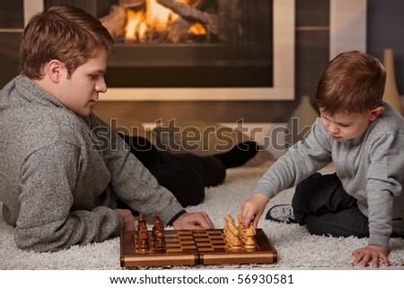 Father and 4 years old kid playing chess at home in a cold winter day. - stock photo