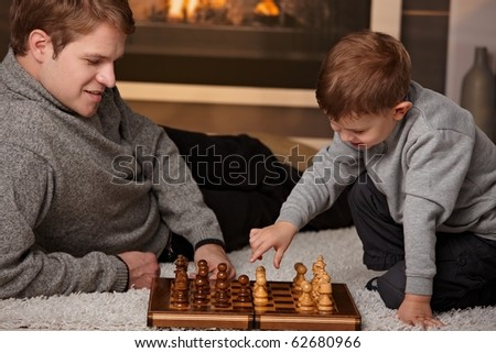 Father and 4 years old son playing chess at home in a cold winter day. - stock photo