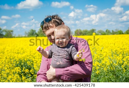 Father and young daughter. Happy family together at meadow outdoor. large family. summer landscape, happiness Rape on the field in summer. Bright Yellow rapeseed oil. Flowering rapeseed. Sunny field.  - stock photo
