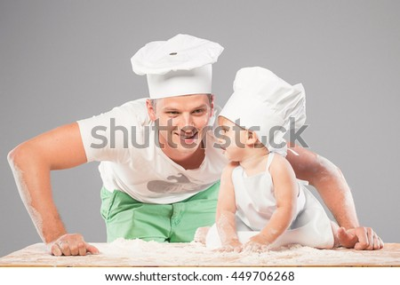 Father and young son dressed as chefs preparing a meal together. The boy helps dad to knead the dough from flour.