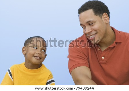 Father and young son smiling and looking at each other - stock photo