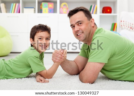Father arm wrestling with his boy - happy family time together