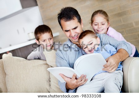 Father at home reading a book to his children