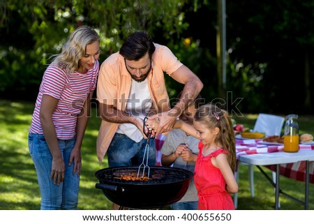 Father besides mother teaching children to barbecue food at yard