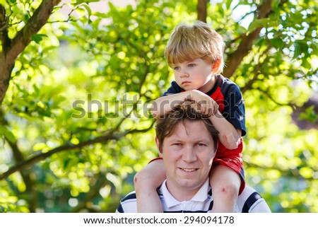 Father carrying child on his shoulders in the park. Little blond kid boy is sad. - stock photo