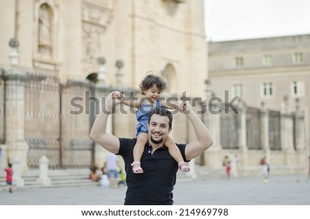 Father carrying daughter on shoulders with city cathedral background - stock photo