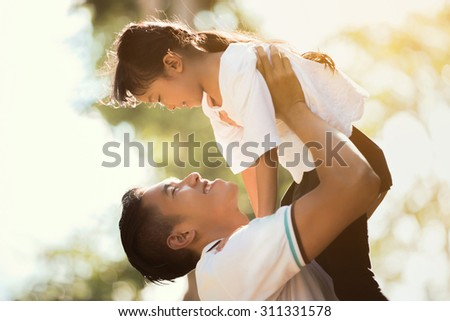 Father carrying daughter Up looking at each other Happily, the early morning hours - stock photo