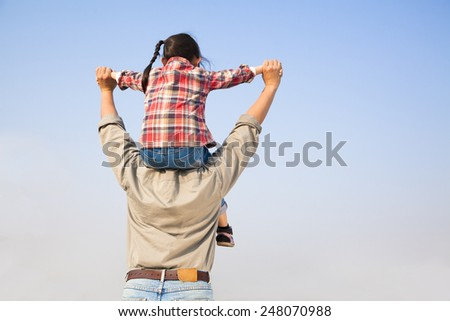 Father carrying his daughter on shoulders with blue sky background - stock photo
