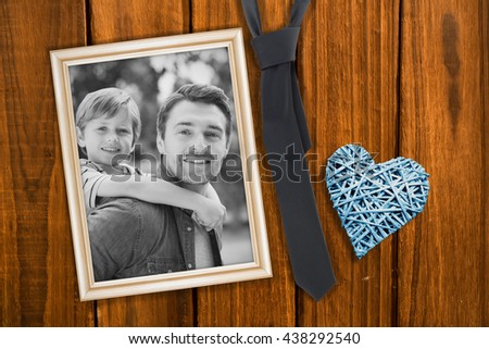 Father carrying young boy on back at park against overhead of wooden planks - stock photo
