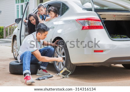 Father change tire and his family waiting between trip and accident was occured. - stock photo