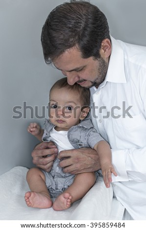 Father changing and dressing up the baby in the baby room - stock photo