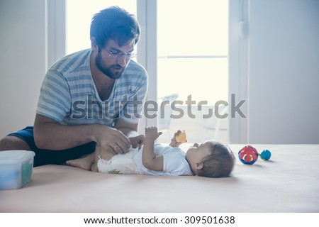 Father Changing Diaper To His Son - stock photo