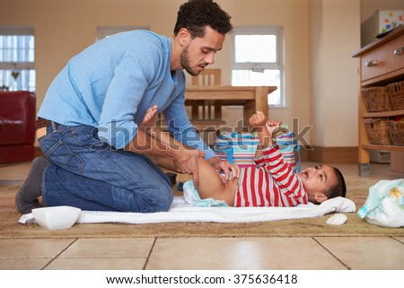 Father Changing Son's Diaper At Home - stock photo