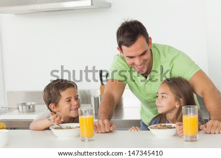 Father chatting to his children while they are having breakfast in the kitchen - stock photo