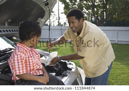 Father checking oil level with his young son
