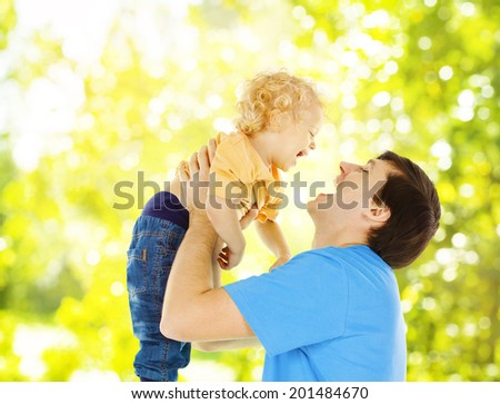 Father child happy playing. Dad raise up smiling son over green abstract background  - stock photo