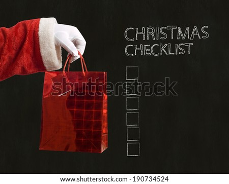 Father Christmas hand holding a red present on blackboard background with checklist - stock photo