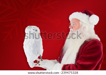 Father Christmas holds an owl against red background