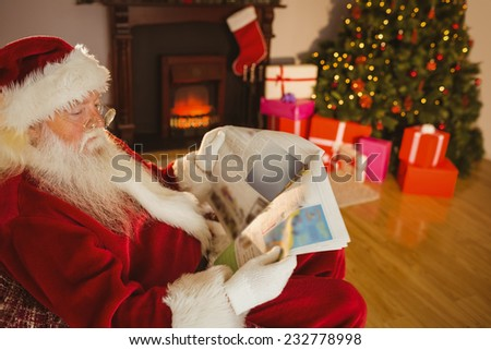 Father christmas reading newspaper on the couch at home in the living room